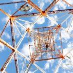 Radiomasto alhaaltapäin kuvattuna pilvistä taivasta vasten.