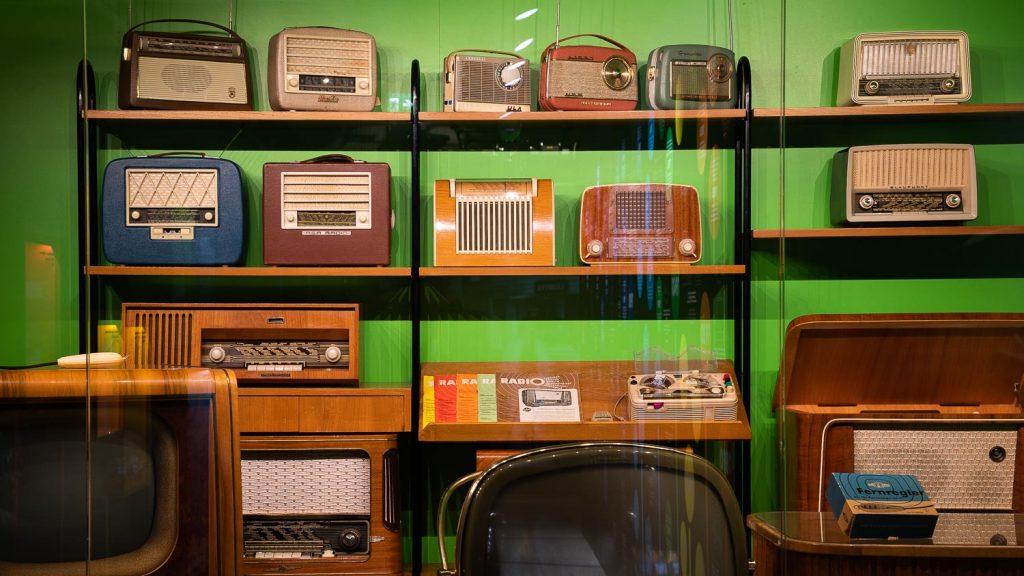 Vanhoja radioita vitriinin hyllyllä.
