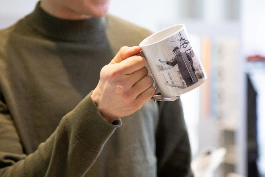 Mies pitelee kädessään mukia, jossa on kuva presidentti Urho Kekkosesta, jonka kädelle on laskeutunut lintu.