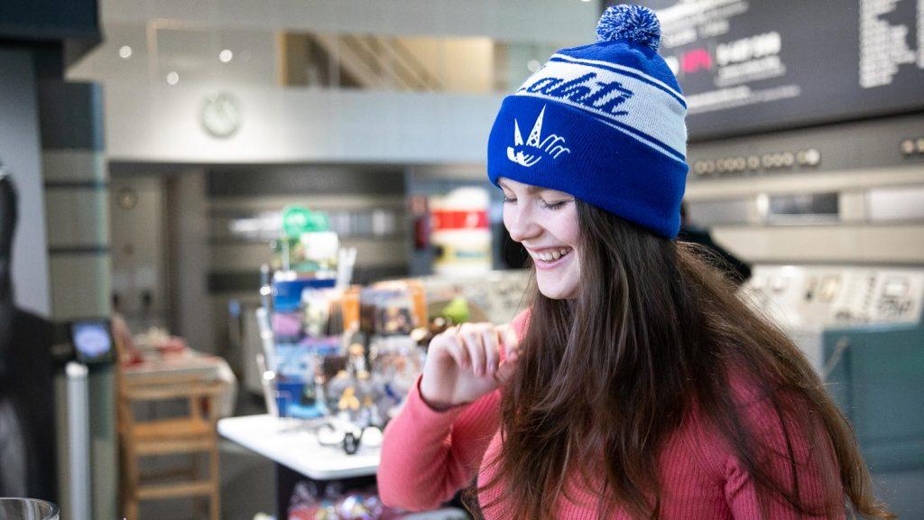 Iloinen nuori nainen Lahti pipo päässään museokaupassa.